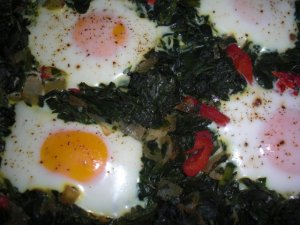 Eggs cooking in the spinach mixture